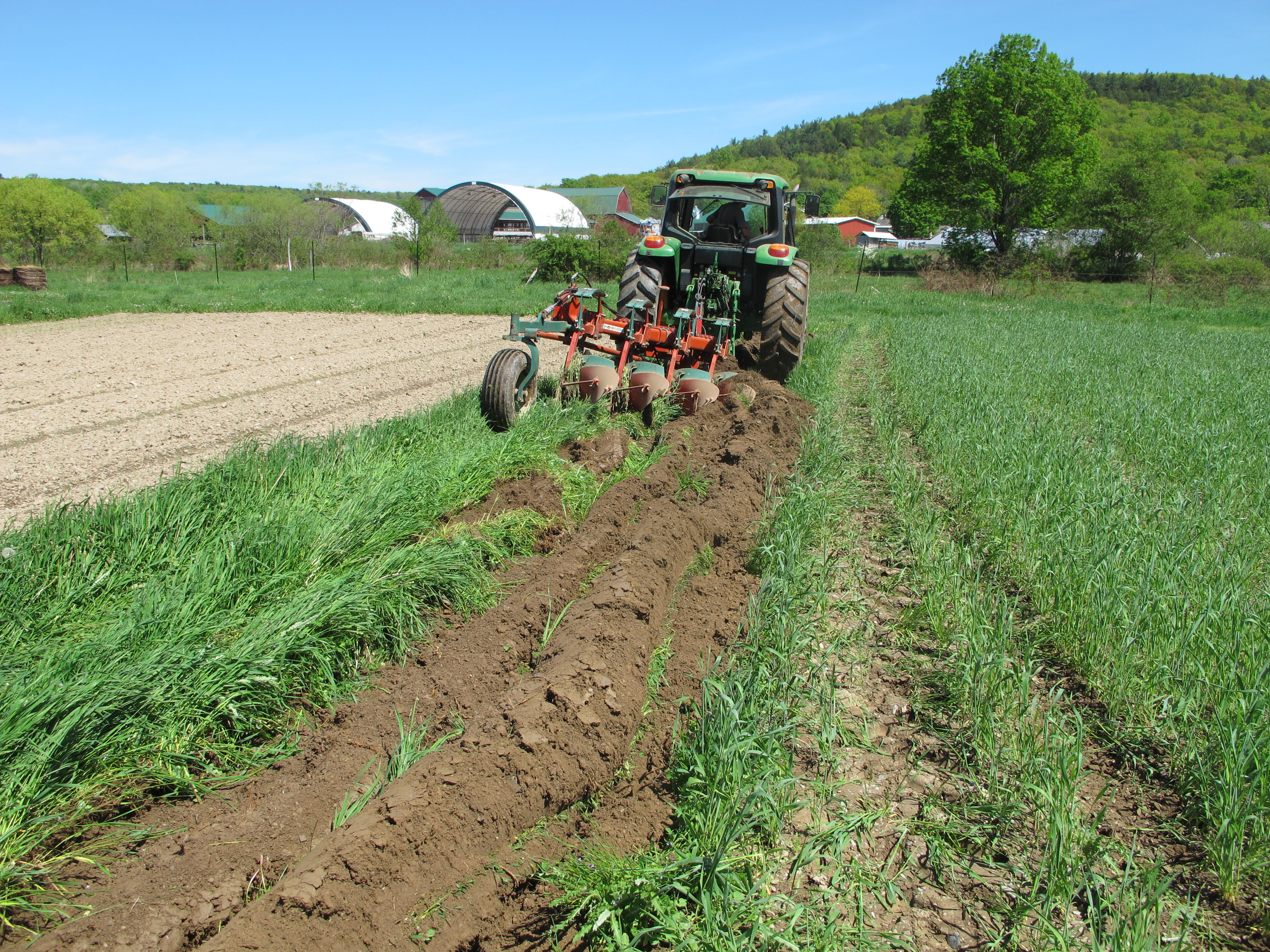 a tractor uses an implement to break up the grass and soil to prepare for planting